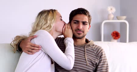 segredo : Blonde whispering a secret to her boyfriend on the couch at home in living room Vídeos