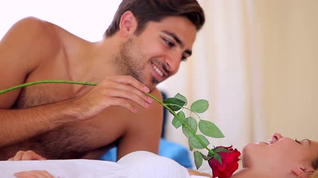 namorado : Man tickling his blonde girlfriend with a rose on bed at home in bedroom