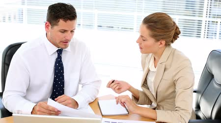 dialog : Business team looking at paperwork together at desk in the office