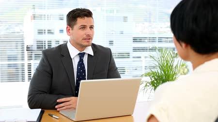 диалог : Businessman with laptop interviewing a woman at his desk in the office
