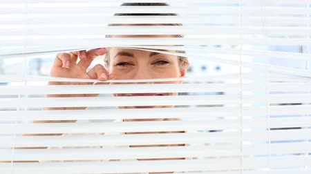 потрясенный : Surprised businesswoman peeking through the blinds in the office