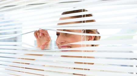 потрясенный : Shocked businesswoman peeking through the blinds in the office