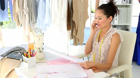 дизайнер : Fashion designer sitting at table talking on phone in her studio