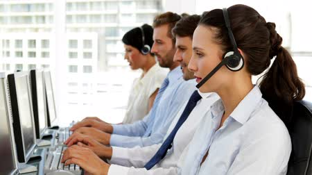 испанец : Happy call centre agent looking to camera in the office Стоковые видеозаписи