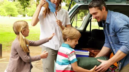 otopark : Family unloading their car for a camping trip on a sunny day Stok Video