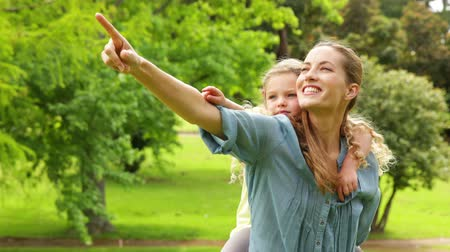 holding : Happy mother giving her daughter a piggy back and pointing on a sunny day Stock Footage