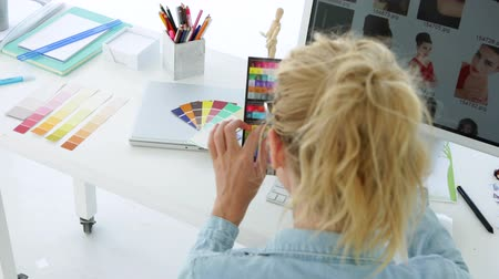 дизайнер : Rear view of blonde designer working at her desk in the office