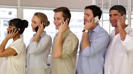 gündelik kıyafetler : Businesspeople phoning while standing in a row in the office Stok Video