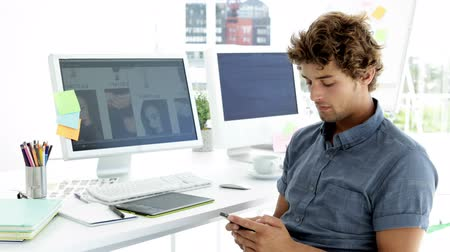 artistas : Handsome creative designer text messaging with his phone in creative office
