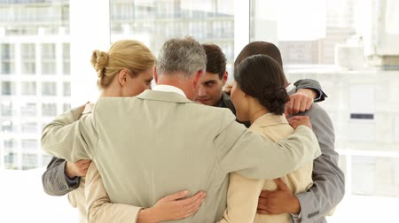 munkatárs : Business people hugging each other in a circle at the office Stock mozgókép