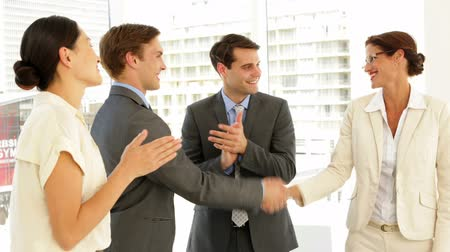 homem de negócios : Business people shaking hands at interview while others applaud at the office