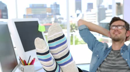 sock : Photo editor smiling with his feet up on his desk in creative office