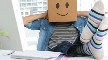 menő : Photo editor wearing smiley face box on his head in creative office Stock mozgókép