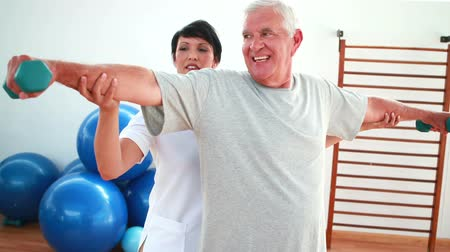 levantamento de pesos : Happy physiotherapist helping elderly patient lift hand weights at the rehabilitation center