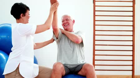 física : Smiling physiotherapist helping elderly patient stretch arm at the rehabilitation center
