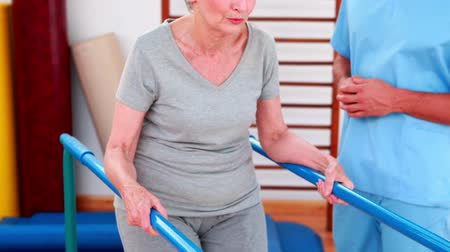 fizjoterapeuta : Physical therapist watching patient walk with parallel bars at the rehabilitation center