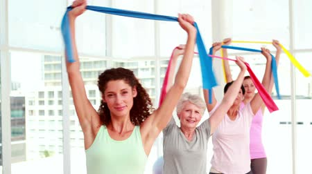esneme : Women stretching resitance bands at a fitness class at the gym