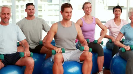 eğitici : Fitness group sitting on exercise balls lifting hand weights at the gym