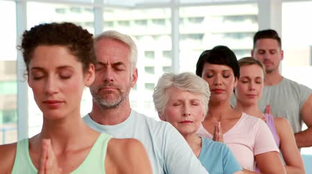 senior lifestyle : Yoga class standing with eyes closed at the gym