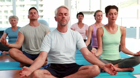 hareketli : Yoga class sitting in lotus position together at the gym Stok Video