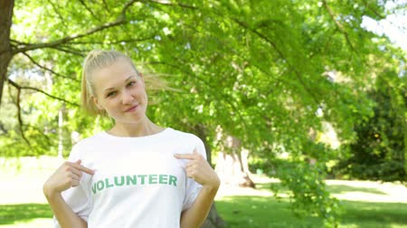 dobrovolník : Pretty blonde volunteer dancing and smiling at the camera on a sunny day