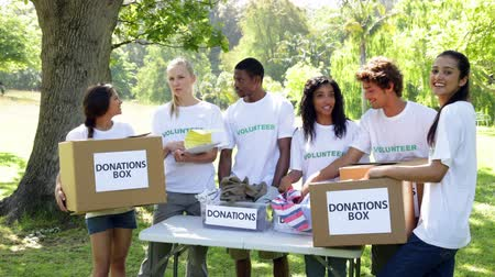 dobrovolník : Group of young volunteers sorting donation boxes on a sunny day