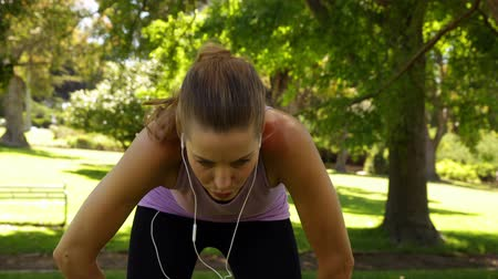 yorgunluk : Runner taking a break to drink water in the park on a sunny day Stok Video