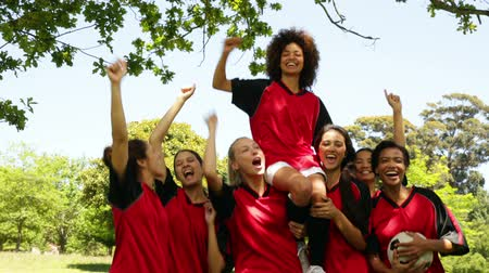 diadal : Female football team celebrating a win in the park on a sunny day