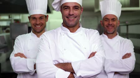сотрудники : Three smiling chefs looking at camera making ok sign in a commercial kitchen