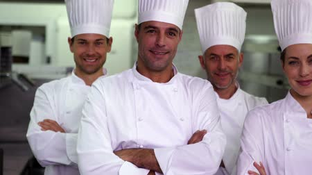 сотрудники : Four happy chefs looking at camera with arms crossed in a commercial kitchen