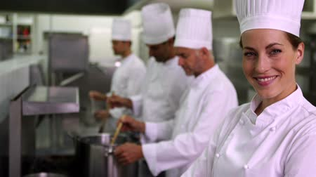 chef : Head chef smiling at camera with team behind her in a commercial kitchen