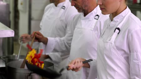 chef cooking : Chef tossing stir fry smiling at camera in a commercial kitchen Stock Footage