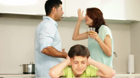 sinir : Upset boy covering his ears while his parents fight at home in the kitchen