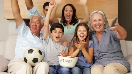 наслаждаться : Happy extended family watching football on tv at home in the living room
