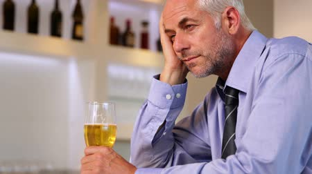 apprehensive : Worried businessman drinking a beer after work at the local bar