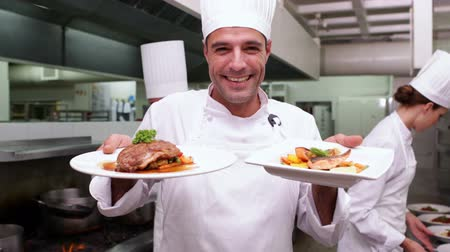 szolgáló : Smiling handsome chef showing two dishes to camera in a commercial kitchen