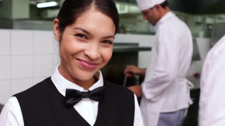 prepare food : Smiling waitress being handed a dish by chef in a commercial kitchen Stock Footage