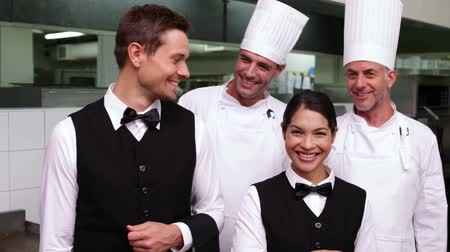 сотрудники : Happy restaurant staff smiling at camera in a commercial kitchen