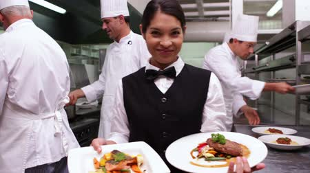 porce : Smiling waitress showing two dishes to camera in a commercial kitchen
