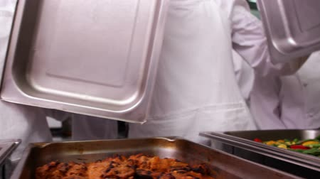 garçonete : Row of chefs lifting lid off serving trays in a commercial kitchen Vídeos