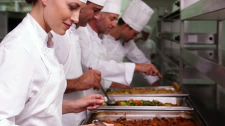 prepare food : Row of chefs preparing food in serving trays in a commercial kitchen Stock Footage