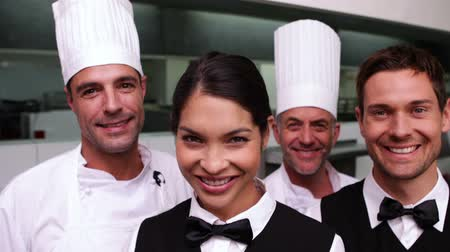 garçonete : Cheerful restaurant staff smiling at camera in a commercial kitchen