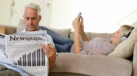 ler : Man reading paper while partner is listening to music on the couch at home in the living room Vídeos