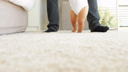 helping : Father helping baby to walk across rug at home in bedroom Stock Footage