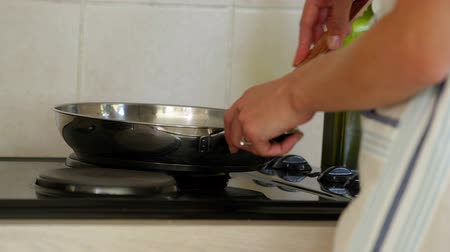 straining : Woman straining pot of water into the sink at home in the kitchen
