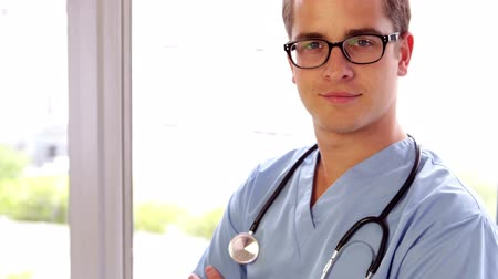 smile : Young surgeon smiling at camera with arms crossed in his office at the hospital Stock Footage