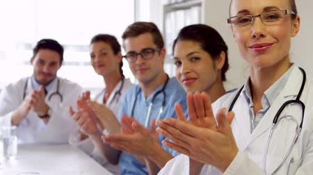 скрабы : Medical team clapping at camera in the board room at the hospital