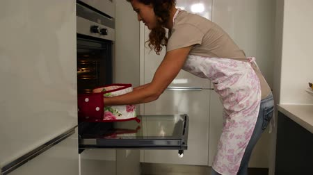 kötény : Woman taking hot cookies out of the oven at home in the kitchen Stock mozgókép