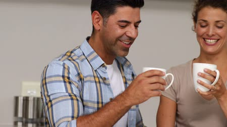 bochecha : Couple drinking coffee and chatting at home in the kitchen