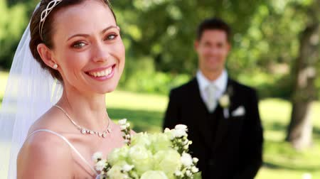 koca : Pretty bride smiling at camera with groom standing in background on a sunny day